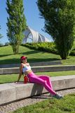 Fit middle-aged woman resting after training in park Stock Photos