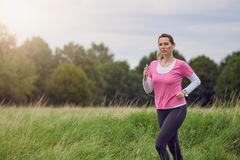 Fit middle-aged woman running through a rural field. Listening to music on her mobile phone using earbuds looking to the side with a happy smile in a healthy Stock Photos