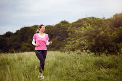 Fit middle-aged woman walking through a rural field Stock Photo