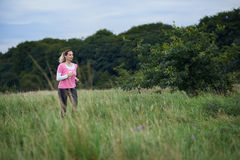 Fit middle-aged woman walking through a rural field Royalty Free Stock Images