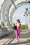 Fit middle-aged woman walking after training in park. Female athletic runner in park in the summer, walking after a jog, fitness and healthy lifestyle concept Royalty Free Stock Images
