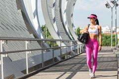 Fit middle-aged woman walking after training in park. Female athletic runner in park in the summer, walking after a jog, fitness and healthy lifestyle concept Royalty Free Stock Photography