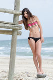 Fit model against life guard tower. Fit model with long brunette hair standing against life guard tower shows off her perfect body, sea and sky as background royalty free stock photography