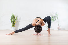 Fit modern dancer standing gracefully on tiptoe in wide side lunge facedown pose indoors. Royalty Free Stock Image
