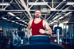 Muscle man running on treadmill. Royalty Free Stock Image