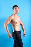 Fit and muscular Asian man in black denim Royalty Free Stock Images