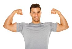 Fit and muscular man flexing his biceps on white royalty free stock image
