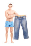 Fit muscular man holding apair of jeans stock photo