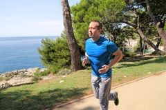 Fit muscular man jogging on a running trail along seashore. Recreational fitness athlete in sportswear enjoys physical activities. Fit muscular man jogging on a Stock Image