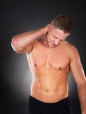 Fit muscular man massaging his neck in pain Royalty Free Stock Photos