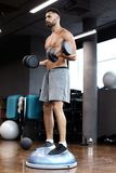 Fit and muscular man working out with bumbbells on gymnastic hemisphere bosu ball in gym.  royalty free stock images
