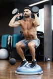 Fit and muscular man working out with bumbbells on gymnastic hemisphere bosu ball in gym.  royalty free stock photo