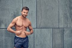 Fit muscular shirtless young man pinching his belly skin. In a concept of belly fat as he stands against a grey urban wall looking at the camera with a friendly Royalty Free Stock Photography