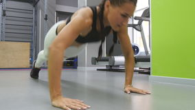 Fit muscular woman doing push ups with steps at the gym. Young sporty girl training at heath club. Female athlete doing