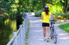 Fit muscular woman wheeling her bicycle outdoors. Fit muscular woman wheeling her bicycle along a road alongside a canal or river with leafy greenery outdoors Stock Images