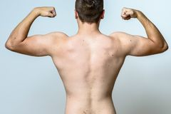 Fit muscular young man flexing his muscles. Raising his arms with clenched fists viewed unclothed from the rear over grey Stock Photos