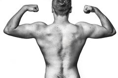 Fit muscular young man flexing his muscles. Raising his arms with clenched fists viewed unclothed, black and white Royalty Free Stock Image