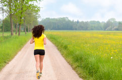 Fit muscular young woman jogging in farmland Stock Image