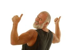 Fit older man. In a tank top throwing thumbs up while flexing; isolated on white Royalty Free Stock Photo