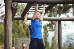 Fit people climbing monkey bars. In bootcamp stock images