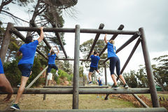Fit people climbing monkey bars in bootcamp Stock Photo