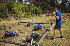 Fit people crawling under the net during obstacle course Stock Photography