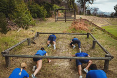 Fit people crawling under the net during obstacle course Royalty Free Stock Photo