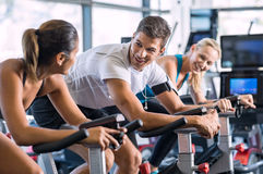 Fit people cycling at gym. Young people talking and smiling while working out on bike at gym. Friends in a conversation while cycling on stationary bike in Stock Photography