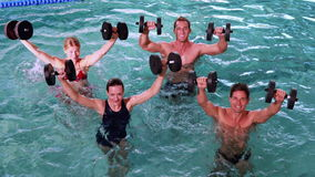 Fit people doing an aqua aerobics class in swimming pool with foam dumbbells Stock Photo