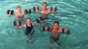 Fit people doing an aqua aerobics class in swimming pool with foam dumbbells Royalty Free Stock Photography