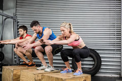 Fit people doing exercises with box Stock Photo