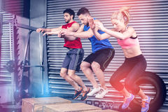Fit people doing exercises with box Royalty Free Stock Images