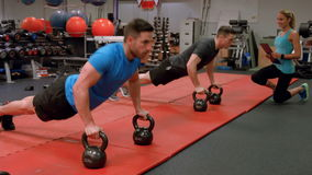 Fit people doing push ups in gym stock video footage