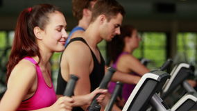 Fit people on elliptical bike. At gym stock video