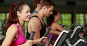 Fit people on elliptical bike. At gym stock video footage