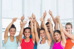 Fit people gesturing thumbs up in exercise room Royalty Free Stock Images