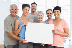 Fit people holding blank board in yoga class Royalty Free Stock Photo