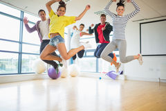 Fit people jumping in bright exercise room Royalty Free Stock Photo
