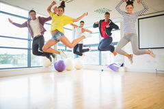 Fit people jumping in exercise room Royalty Free Stock Images