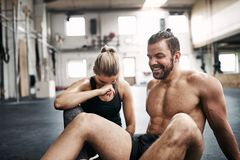 Fit people laughing while taking a break from working out. Smiling young people in sportswear sitting on a gym floor laughing together while taking a break from stock photos