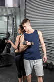Fit people lifting dumbbells back to back Stock Photography