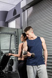 Fit people lifting dumbbells back to back Stock Images