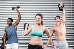 Fit people lifting dumbbells stock photography