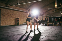 Fit people lifting weight discs in gym Royalty Free Stock Photo