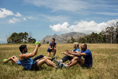 Fit people performing core exercise. In bootcamp stock photography
