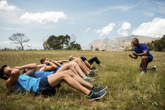 Fit people performing crunches exercise. In bootcamp Stock Photography
