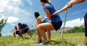 Fit people playing tug of war during obstacle training course 4k. Fit people playing tug of war during obstacle training course in boot camp 4k stock video footage