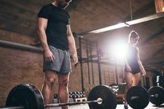 Fit people preparing themselves before lifting barbells