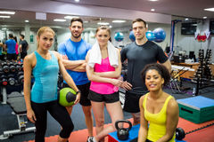 Fit people smiling at camera in weights room Stock Photos