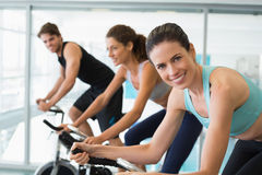 Fit people in a spin class with brunette smiling at camera Royalty Free Stock Photography